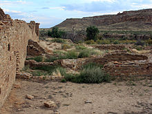 A partly overcast sky and subdued sunlight over a roughly six-foot tall wall of dusky tan sandstone bricks which vary somewhat in size. The wall runs diagonally from the immediate foreground at left towards the right, running perhaps several dozen feet to the near middle distance. A few feet to the right, in the middle foreground, a low ring of similar blocks delimits a circular pit sunk into the ground. The remains of several other ruinous low walls, perhaps one to three high at most, are arrayed in parallel; they align left to right from the high diagonal wall. Perhaps a mile distant to the center and right, a canyon wall slopes gradually level to meet the valley floor on which the walls sit.