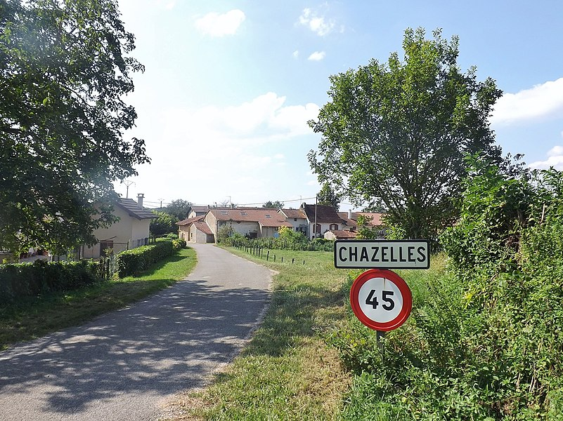 Sight of an old road sign welcoming visitors to the French commune and village of Chazelles, in Jura. Since a 2016 merger, this village is part of Les Troix-Châteaux commune.