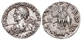 """Antialcidas - Silver tetradrachm of King Antialcidas. Obv: Bust of Antialcidas wearing aegis and holding a spear, with Greek legend BASILEOS NIKEPHOROU ANTIALKIDOU """"Of Victorious King Antialcidas"""".  Rev: Zeus with lotus-tipped sceptre, in front of an elephant with a bell (symbol of Taxila), surmouted by Nike holding a wreath, crowning the elephant. Kharoshti legend: MAHARAJASA JAYADHARASA ANTIALIKITASA """"Victorious King Antialcidas"""". Pushkalavati mint."""