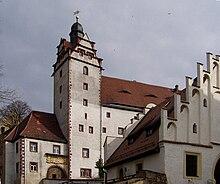 um edifício caiado de branco com telhado de telhas vermelhas, parte do Castelo Colditz