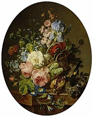 Open wicker basket of mixed flowers, including iris, roses, poppies, hollyhock, marygold, larkspur and convolulus on a marble ledge with an open pomegrante and a goldfinch with its nest