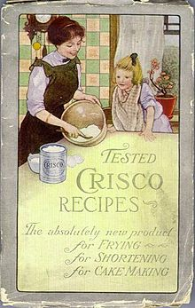 Cover of the 1912 Crisco Cookbook: In a kitchen, a woman mixes something in a bowl while a girl watches