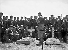 A group of men in military uniform gathered around a grave.