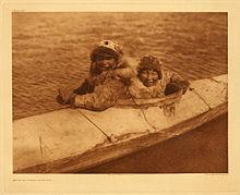 Фотография двух самцов в мехах, сидящих в колодце большой байдарки