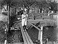 Een boerin met een lammetje in haar armen op een smalle loopbrug voor de boerder, Bestanddeelnr 189-0279.jpg