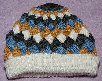 Knitted fabric - Illustration of entrelac.  The blue and white wales are parallel to each other, but both are perpendicular to the black and gold wales, resembling basket weaving.