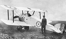 Uniformed man in peaked cap standing in front of white biplane