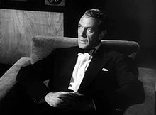 Black and white screen capture of Gary Cooper, seated and wearing a black tuxedo