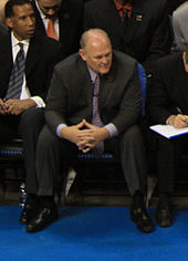 A man with gray hair, wearing a black suit, white shirt and tie, sitting at a basketball game.