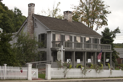 A light gray wooden house, five bays wide, with darker gray shutters, seen from its front right. It has a second-story balcony across the front supported by wooden pillars, two brick chimneys and a white picket fence with open gate in front.