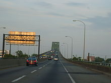 A four lane freeway ascending onto a continupus arch bridge