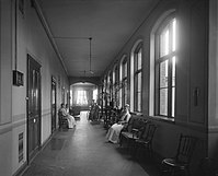 Old photograph of a hallway with people sitting