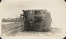 An interurban railcar lays on its side off of its tracks