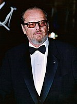 A Caucasian man is seen wearing sunglasses, a black suit over a white collared shirt and a black bowtie.