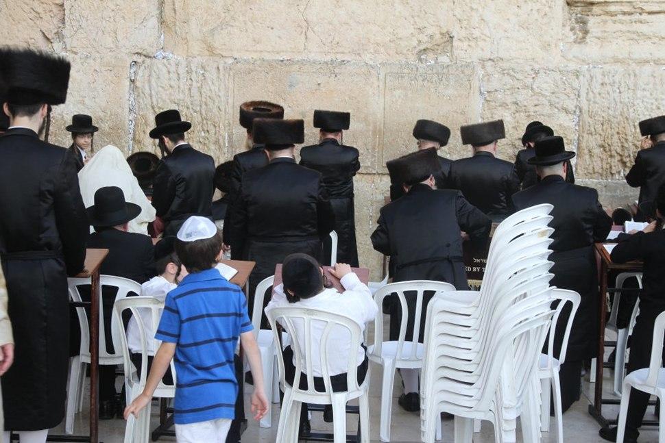 Jewish men pray at the western wall