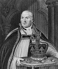 A middle-aged man wearing clerical robes and gown carrying a decorated cushion, upon which rests a large bejewelled crown