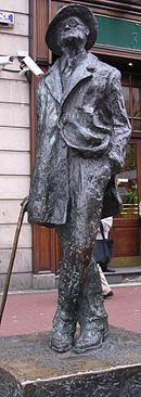 Bronze statue of Joyce standing in a coat and broadbrimmed hat: His head is cocked looking up, his left leg is crossed over his right, his right hand holds a cane, and his left is in his pants pocket, with the left part of his coat tucked back.