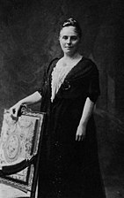 A posed formal black and white photograph of a woman standing behind a chair upon which she is resting her hand