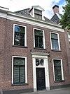 foto van Pand met lijstgevel op plint met door pilasters en kroonlijst omlijste voordeur en dakkapel met omlijsting