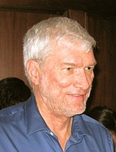 A man with gray hair and a thin, gray beard