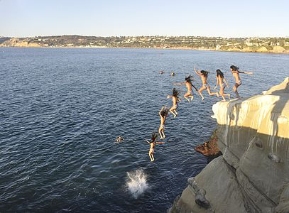 Cliff jumping near the big cave at La Jolla Cove, with La Jolla Shores in the background.