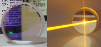 Output coupler - A dielectric output-coupler for a dye laser. Centered at 550 nm, the left photo shows its high reflectance to yellow light and its high transmittance to red and blue light. The right photo shows it reflecting 75% of a laser beam and transmitting 25%, although the beam appears brighter when moving toward the observer than when moving away.