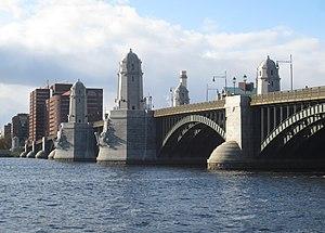 Un puente con arcos de metal y pilares de piedra sobre un ancho río.