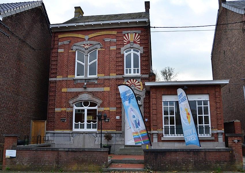 La façade principale et la toiture de la maison Art Nouveau sise rue des Écoles, n°26 à Pont-a-Celles, (à l'exception de l'annexe droite) ainsi que le vitrail de la porte de la façade arrière (M) une zone de protection est étabie autour de cette maison (ZP)