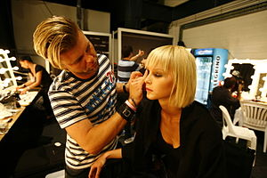 Make-up artist backstage at the Fashion Assass...