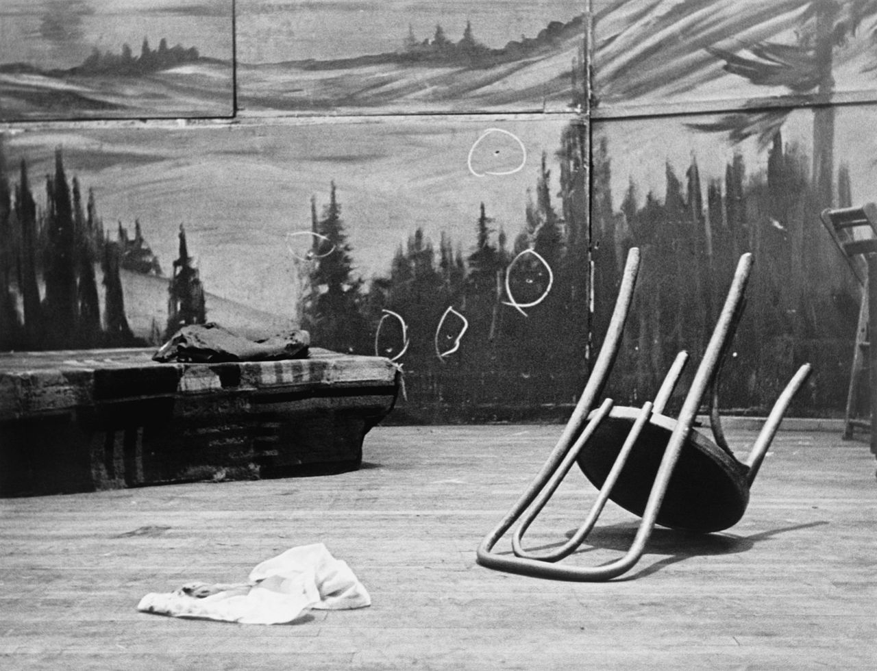 An overturned chair in front of a mural, on which several chalk circles have been drawn around bullet-holes