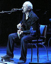 Image of Mark Knopfler sitting in a chair onstage playing guitar and singing
