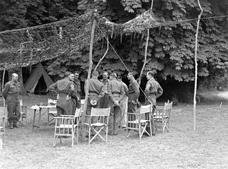 Battle of Verrières Ridge - Montgomery (eighth from left) talking with Simonds (ninth from left) at II Canadian Corps Headquarters in Normandy, France, 20 July 1944. Photo by Lt. Donald I. Grant