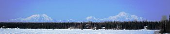 A panorama showing, from left to right, Mount Foraker, Mount Hunter, and Mount McKinley. Some cabins are at the edge of an evergreen forest.