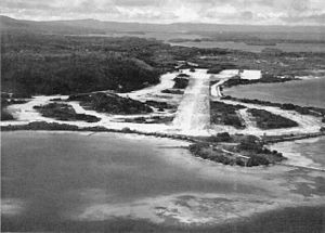 Munda Airport - Looking eastward, over Munda Field, toward the scene of battle, this post-war picture shows how the jungle has already begun to encroach on what was the busiest Allied airstrip in the Solomons. Within a year dense vegetation had already obscured Bibilo Hill, while once bare Kokengolo (to the center left of the photograph) sprouts a thick growth.