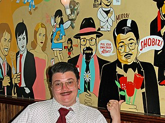 "East Village, Manhattan - Performer Murray Hill with the ""Downtown Legends"" wall at Mo Pitkins' House Of Satisfaction, depicting artists of the East Village performance scene, including the Reverend Jen, Nick Zedd, Allen Ginsberg, Reverend Billy"