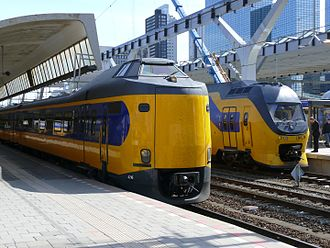 Trains in the Netherlands - Two current Dutch Railways InterCity trains: a refurbished ICM train in the foreground, and the front of a VIRM double decker behind it. Photo taken during the rebuild of Rotterdam Central station; in the background the current overall roof is taking shape, while the foreground still shows one of the old individual platform covers