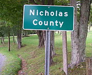 A highway sign designating the border between Nicholas and Greenbrier counties in West Virginia along a secondary road.