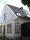 foto van Houten dijkhuis met puntgevel, onderpui met fries in empirestijl, overhoeks geplaatst raam