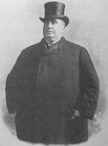 A large man stands wearing a full length coat and top hat.