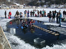 A diver is visible underwater in a hole cut in the ice cover of a small lake. Blocks of ice cut to form the hole are stacked to one side, and a second diver sits on the edge of the hole with his legs in the water. A rough wooden ladder bridges the hole. The dive site is cordoned off with a red and white tape, and other members of the support team stand to the side, with onlookers outside the cordon.