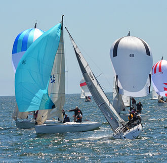 Sailing - Aerodynamic force components for two points of sail.  Left-hand boat: Down wind with detached air flow like a parachute— predominant drag component propels the boat with little heeling moment.  Right-hand boat: Up wind (close-hauled) with attached airflow like a wing—predominant lift component both propels the boat and contributes to heel.