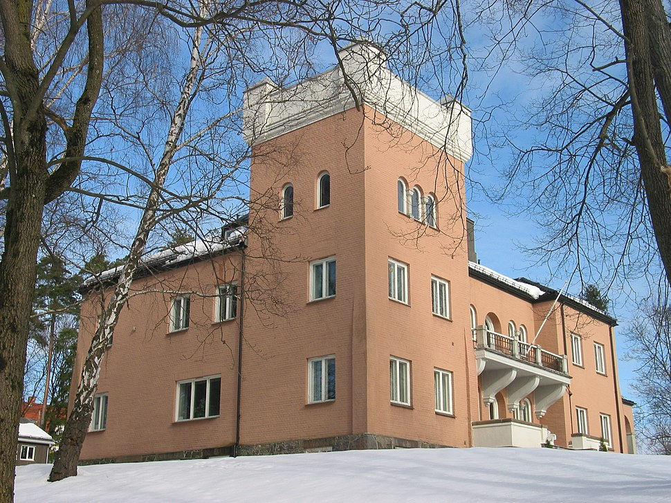 A substantial building in pink stone or cladding, consisting of a three-storey square tower with two two-storey wings. The building stands, framed by trees, in a snow-covered garden.