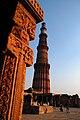Qutb Minar, and detailing of pillared cloister of Quwwat ul-Islam mosque.jpg