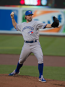 "A man wearing a gray baseball uniform with blue socks, ""Toronto"" written across the chest in blue letters, and a blue cap prepares to throw a baseball from the pitcher's mound"