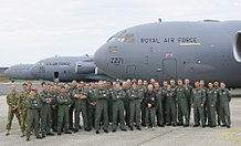 A group of people wearing overalls standing together in front of three large grey aircraft.