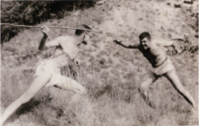 Sepia-toned photograph of two teenagers posing as if fighting, one on the left holding a stick as a spear.