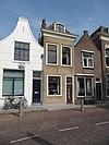 foto van Smalle lijstgevel voor huis van parterre en verdieping met schilddak, waarin dakvenster met geprofileerd, gelobd fronton Stoep