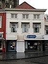 foto van Huis met gebosseerd grijsgepleisterde lijstgevel en hoog schilddak