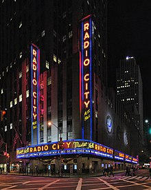 "A building in a city at night that reads ""RADIO CITY"" in all caps lit up in various places around the building"