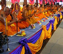 Bhikkhus in saffron robes kneeling in Thailand